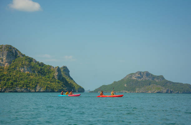 Tourists exploring calm tropical bay with limestone mountains by kayak stock photo