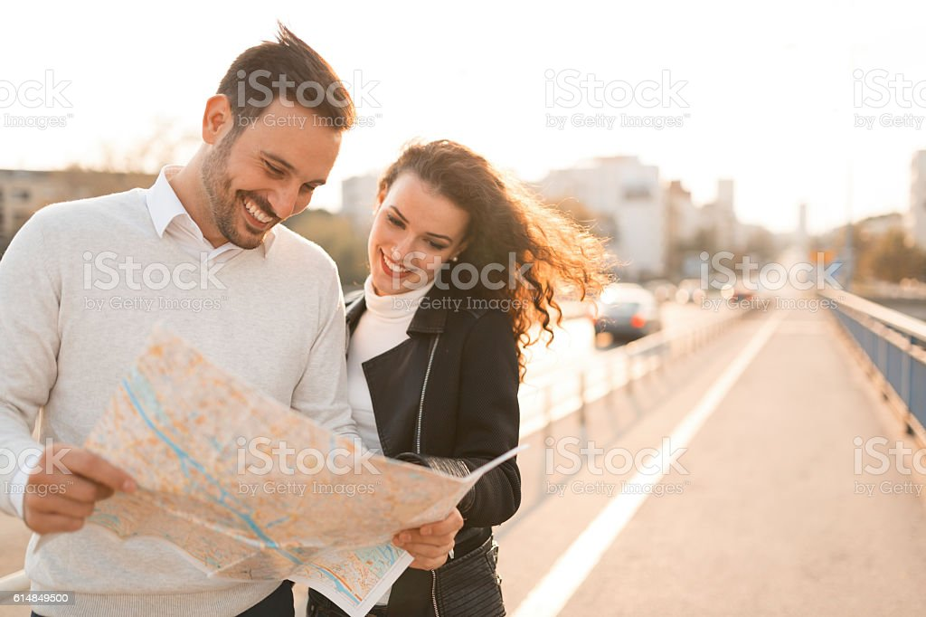 Tourists exploring city by map stock photo