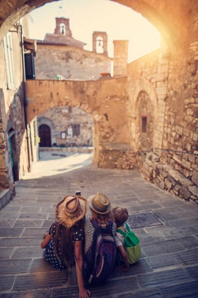 touristen-familie genießen ruhigen straße der italienischen stadt - toskana ferien stock-fotos und bilder