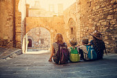 Mother and kids tourists sightseeing beautiful Italian town of Campiglia Marittima. Sunny summer day. Italy, Tuscany.