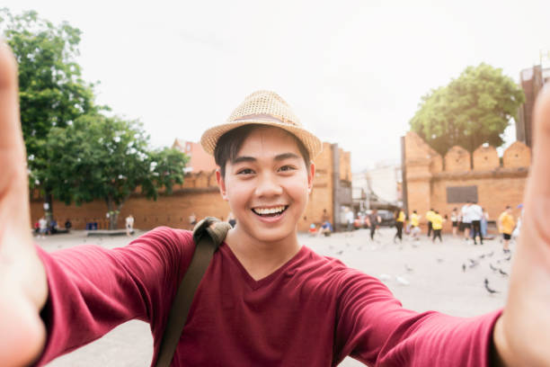 Tourists feeling and happy and fun and use a camera to take a selfie. stock photo