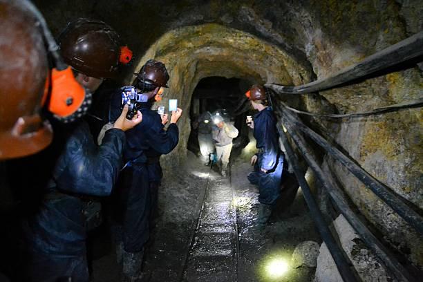 Tourists film miners inside of Cerro Rico mine in Potosi stock photo