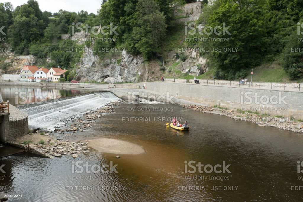 Tourists float along the Vltava River in a a yellow raft below the Castle in the charming medieval town of Cesky Krumlov. stock photo