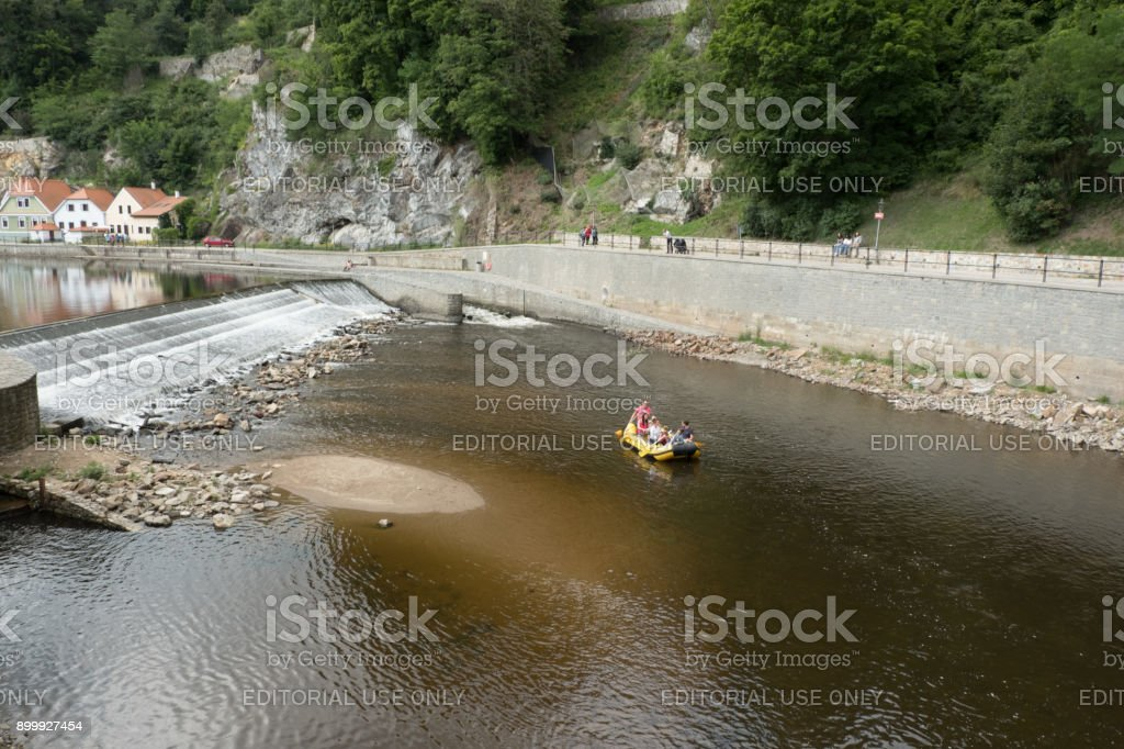 Tourists float along the Vltava River in a a yellow raft in the charming medieval town of Cesky Krumlov. Tourist in a raft below Cesky Krumlov Castle. stock photo