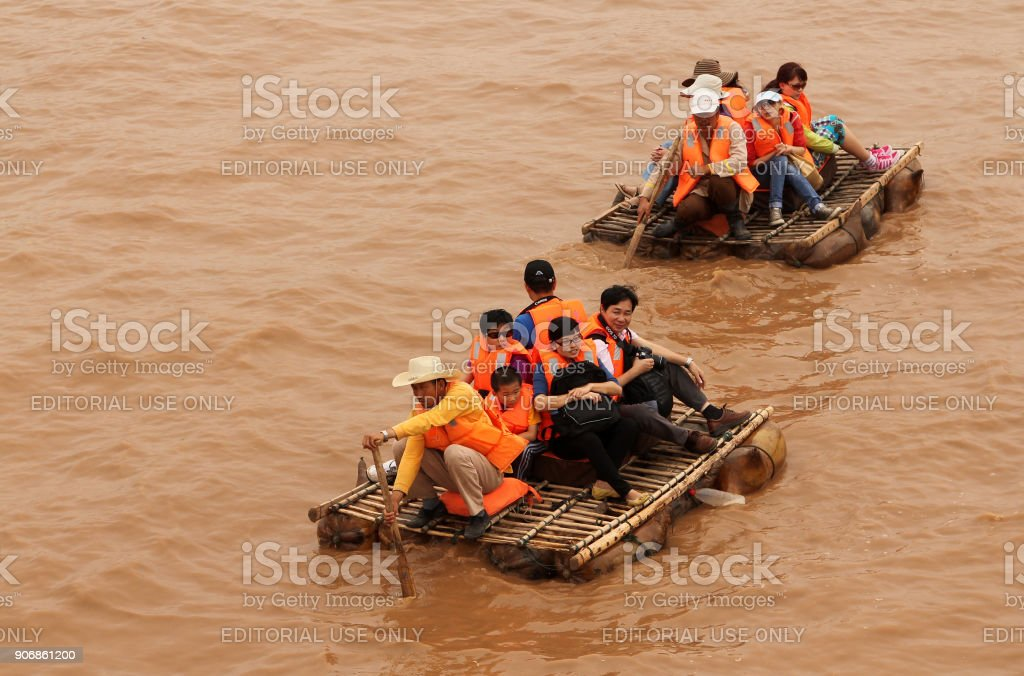 Toeristen zwevend langs de gele rivier (Huang He) op een schapenvacht vlotten, Shapotou toeristisch gebied foto