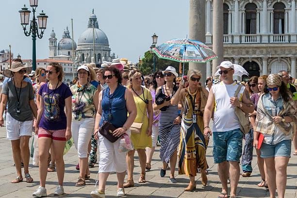 Tourists follow their tour guide through St Mark's Square, Venice stock photo