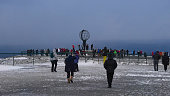 Nordkapp, Norway - 02/28/2019: Tourists from a Hurtigruten cruise ship on a day tour to North Cape gathering around popular globe sculpture above the arctic sea during off-season in winter time.