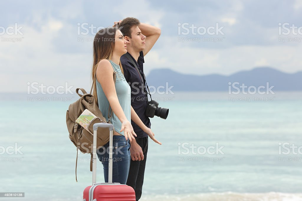 Tourists frustrated with the bad weather on the beach stock photo