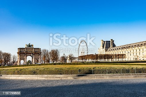 Paris, France - December 4, 2019: Tourists gathered around the iconic landmark Carrousel Arc de Triomphe and Ferris wheel on a bright sunny winters day.
