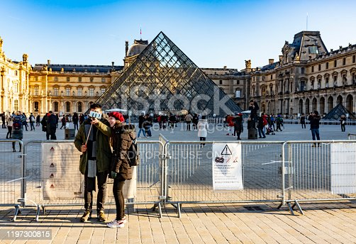 Paris, France - December 4, 2019: Tourists gathered around the iconic landmark Louvre square on a bright sunny winters day with the Louvre in the background.