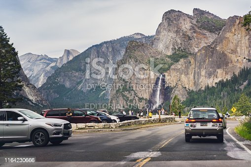 June 27, 2019 Yosemite National Park / CA / USA - Tourists gathered at the Tunnel View vista point; Bridalveil Fall and Half Dome visible in the background