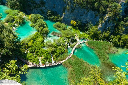 Tourists go on special tracks around the lake in the park Plitvice Lakes, Croatia. Plitvice Lakes - National Park in Croatia, located in the central part of the country. Since 1979, the national park