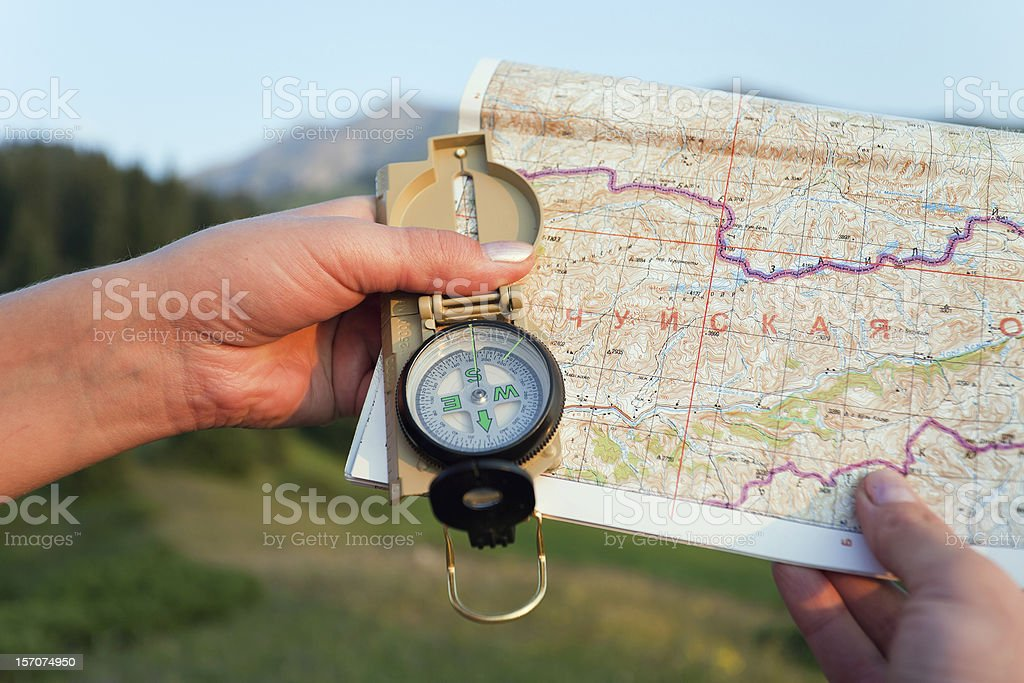 Tourist's hand with map and compass in mountains Switzerland royalty-free stock photo