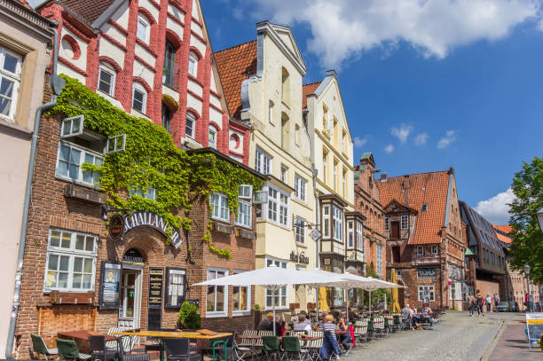 Tourists having a drink at a cafe in the historic harbor of Luneburg Luneburg, Germany - May 21, 2017: Tourists having a drink at a cafe in the historic harbor of Luneburg lüneburg stock pictures, royalty-free photos & images