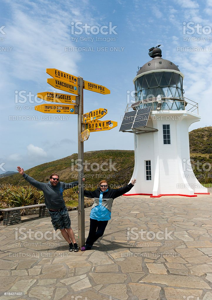 Tourists having fun at Cape Reinga lighthouse in New Zealand stock photo