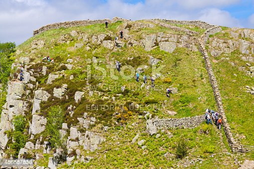 Cumbria, United Kingdom - June 23, 2015: Tourists hiking along Hadrian Wall and climbing rocks. Steep rocky hill with green grass is in foreground. Blue sky with clouds is in background. HDR photorealistic image.