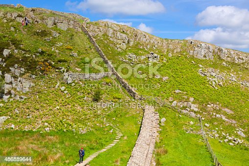 Cumbria, United Kingdom - June 23, 2015: Tourists hiking along Hadrian Wall. Steep rocky hill with green grass is in foreground. Blue sky with clouds is in background. HDR photorealistic image.