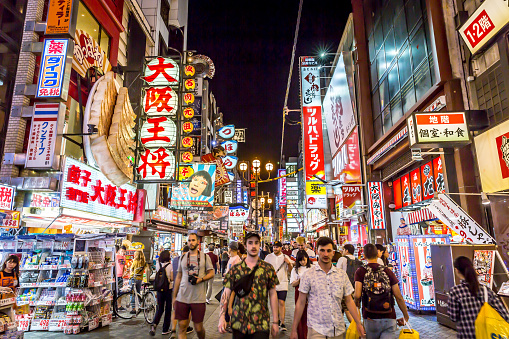Tourists in a busy street in Osaka Downtown, plenty of billboards, colorful scenario, Japan