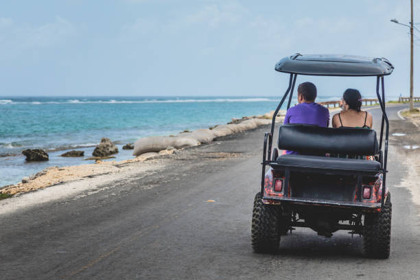 Tourists in a Golf Cart. There is a Road that do the Round Trip All Around the Island. All kind of Vehicles use this Route stock photo