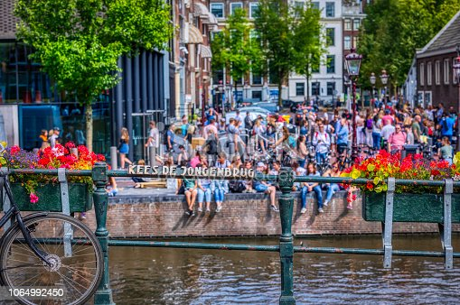 Amsterdam city scene with a lot of tourists resting in the water canals on a sunny day