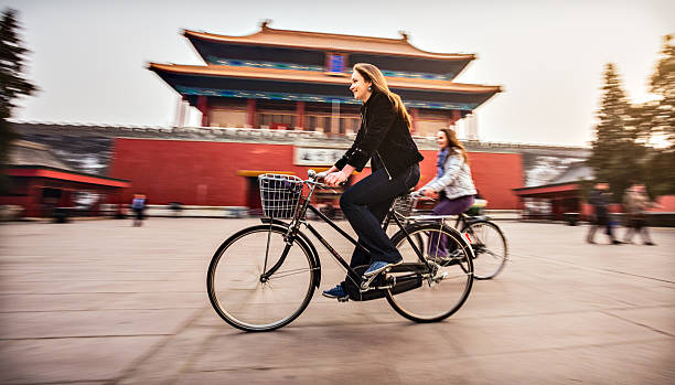 Tourists in Beijing riding bikes Friends riding retro bicycles along forbidden city Bike tour stock pictures, royalty-free photos & images