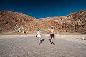 Tourists in Badwater Basin at hot summer day, Death Valley National Park, California, USA.