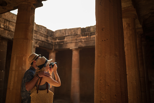 Tourists in Italy taking photos of ancient Roman architecture site