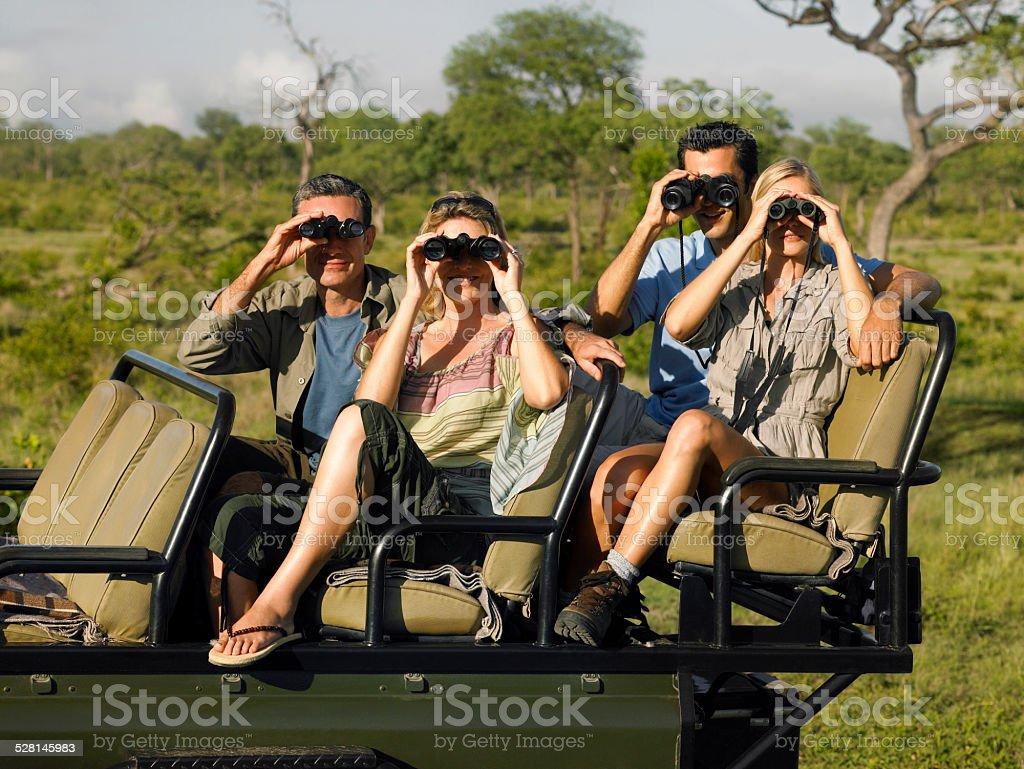 Tourists In Jeep Looking Through Binoculars stock photo