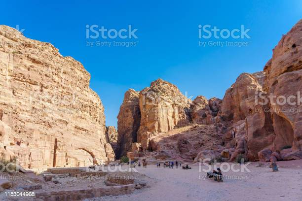 Tourists in narrow passage of rocks of Petra canyon in Jordan, UNESCO World Heritage Site since 1985.
