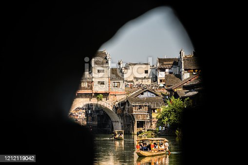 Feng Huang, China -  August 2019 : Group of tourists sailing in old historic wooden boat under the landmark arched bridge on the Tuo river, flowing through the centre of Fenghuang Old Town