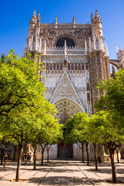 Tourists in Orange tree courtyard in front of Seville Cathedral entrance in Seville, Spain stock photo