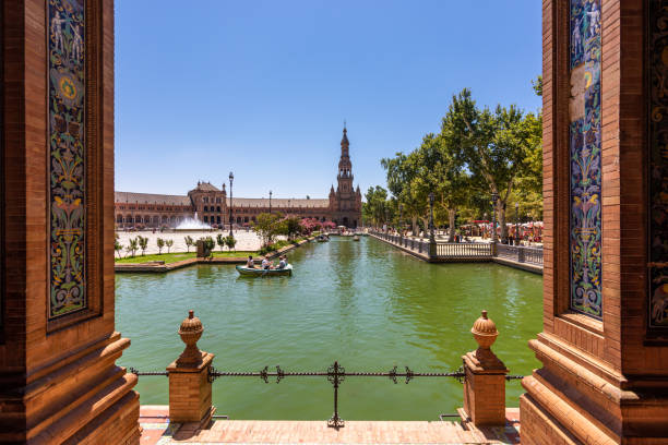 Tourists in rowing boats touring the canals of Plaza de España in Seville, Spain stock photo