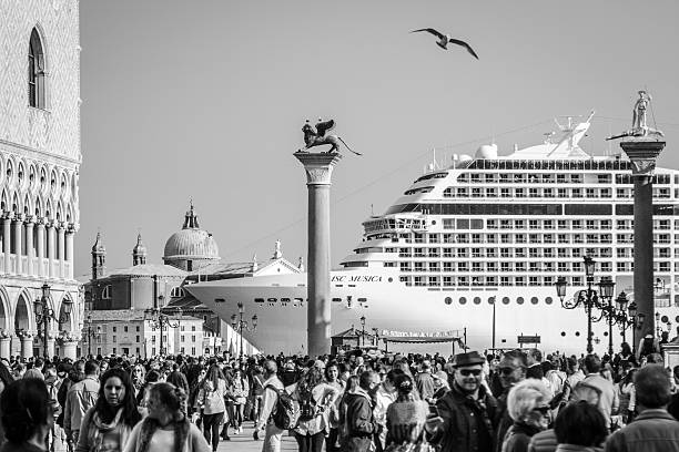Tourists in St Mark's Square as large cruise ship passes stock photo