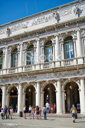 Venice, Italy - June 01, 2019: tourists in St. Mark's Square, outside the Procuratie Vecchie, the oldest of three connected buildings.