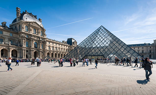 Tourists in the Louvre's central courtyards. Paris, France - April 14, 2013: Tourists in the Louvre's central courtyards with the Louvre pyramid and palace. The Louvre is the world's most visited museum. musee du louvre stock pictures, royalty-free photos & images