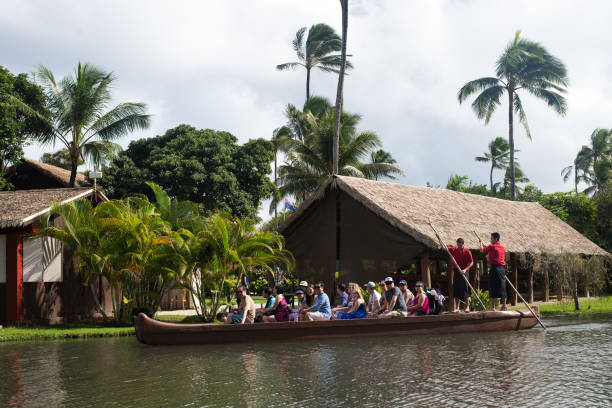 Tourists in the Polynesian Cultural Center, are paddled down the stream on a canoe stock photo