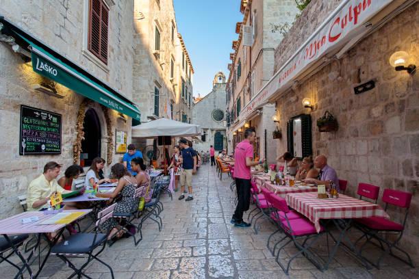 Turistas en restaurantes típicos de la vieja ciudad de Dubrovnik, Dalmacia, Croacia - foto de stock