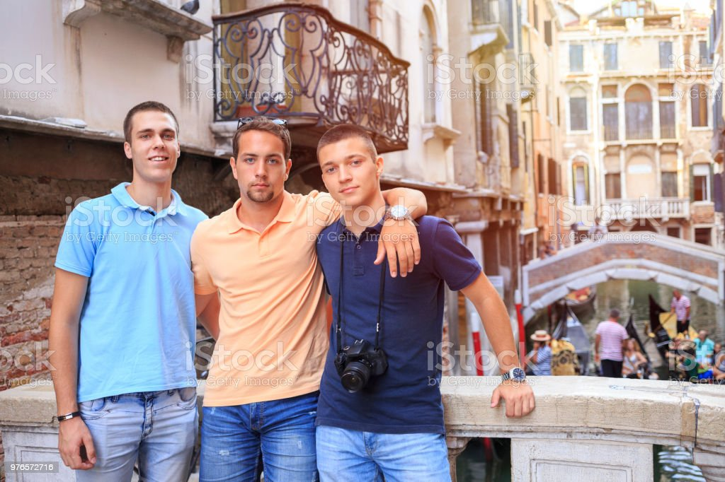 Tourists in Venezia. Three young men, have fun. Group of friends posing for a  photo, Venice. Casual lifestyles Urban scene Italy.  Visiting Venice, Italy. stock photo