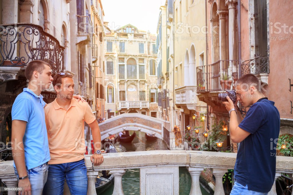 Tourists in Venezia. Three young men, have fun. Group of friends taking a  photo, Venice. Casual lifestyles Urban scene Italy.  Visiting Venice, Italy. zbiór zdjęć royalty-free