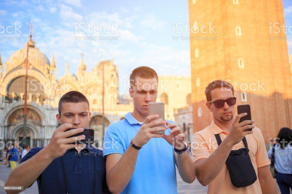 Touristes à Venezia. Trois jeunes hommes, avoir du plaisir. Groupe d'amis, prendre une photo avec le smartphone, la cathédrale de St Mark sur Piazza San Marco, Venise. Scène urbaine de style de vie décontracté Italie.  Visite à Venise, Italie. - Photo de 18-19 ans libre de droits