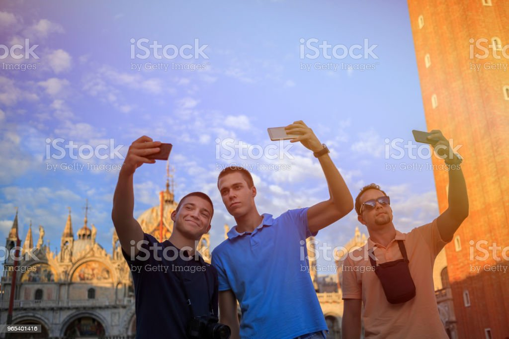 Tourists in Venezia. Three young men, have fun. Group of friends taking a  photo with smartphone, St Mark's Cathedral in Piazza San Marco, Venice. Casual lifestyles Urban scene Italy.  Visiting Venice, Italy. zbiór zdjęć royalty-free