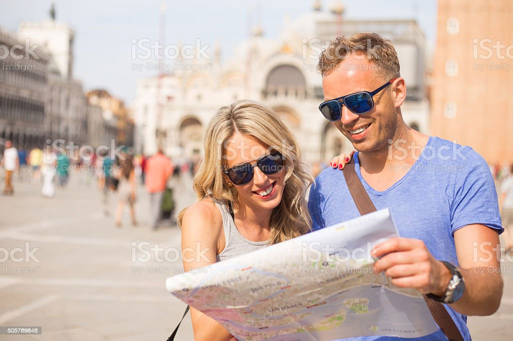 Tourists in Venice looking at city map stock photo