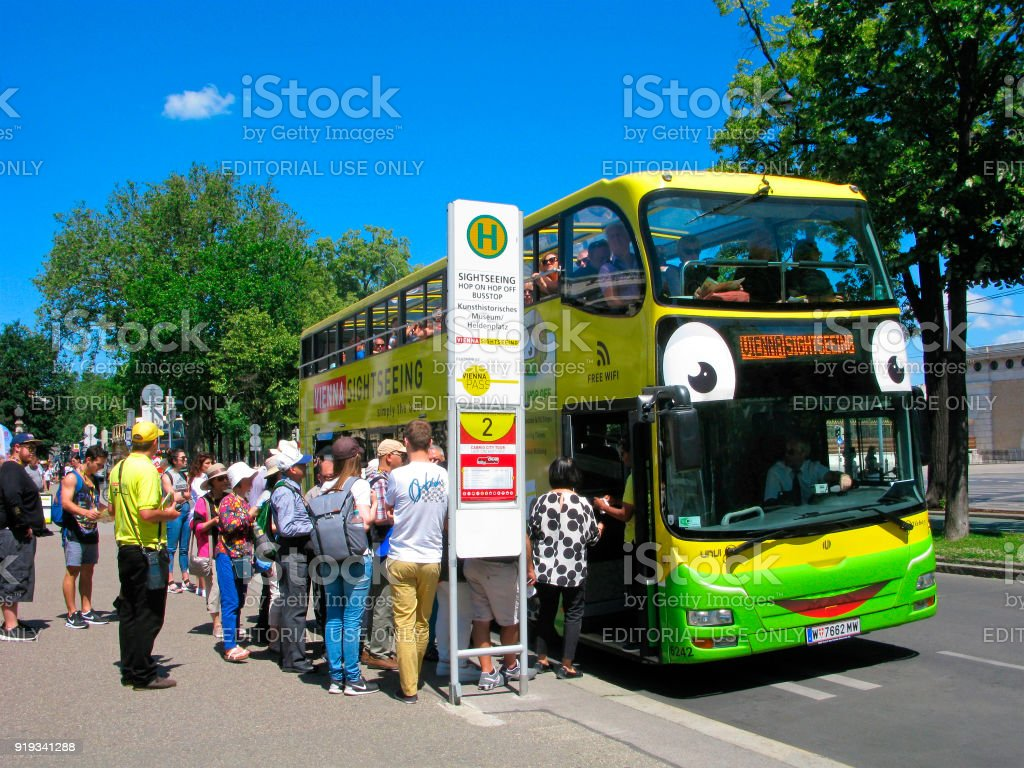 Tourists in Vienna, touristic urban bus, crowd of people on stop