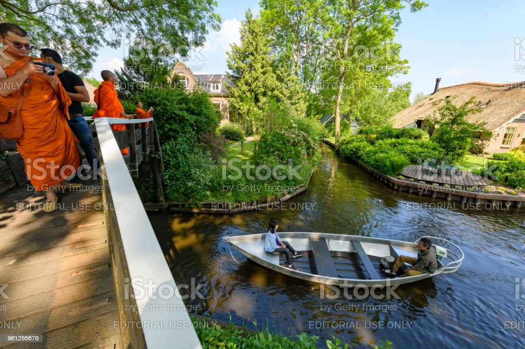 Tourists including buddhist monks enjoying a day around the canals of Giethoorn in The Netherlands stock photo