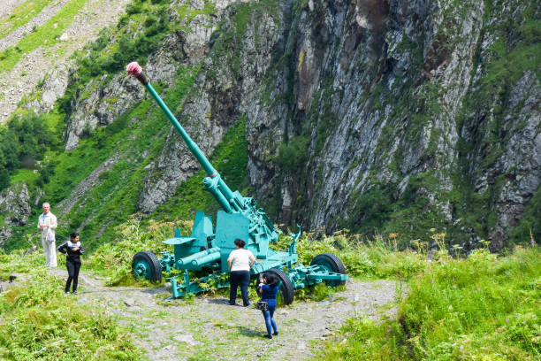 Tourists look at the anti-avalanche cannon in the Tsey gorge in North Ossetia, Russia stock photo