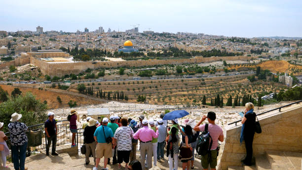 Tourists look at the Jerusalem Old City Jerusalem - May 24, 2017: The guide shows the Jerusalem Old City view to the tourists. Mount of Olives is a famous and sacred Christian's place and it has a fantastic view to the Old Jerusalem. muslim quarter stock pictures, royalty-free photos & images