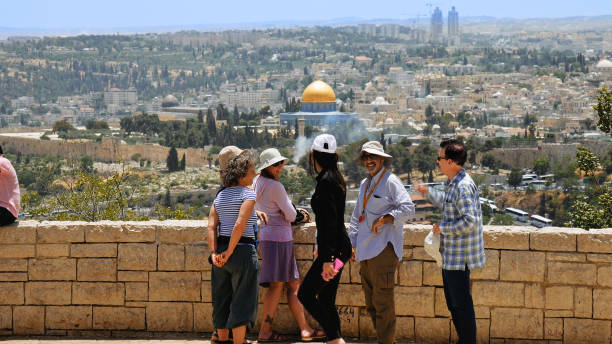 Tourists look at the Jerusalem Old City view Jerusalem, Israel - May 25, 2017: The guide shows the Jerusalem Old City view to the tourists and pilgrims. Mount of Olives is a famous Holy Land place and it has a fantastic view to the Old Jerusalem muslim quarter stock pictures, royalty-free photos & images