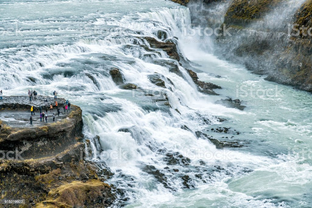 Tourists Looking at a River and its Waterfalls in Iceland - Gullfoss falls stock photo