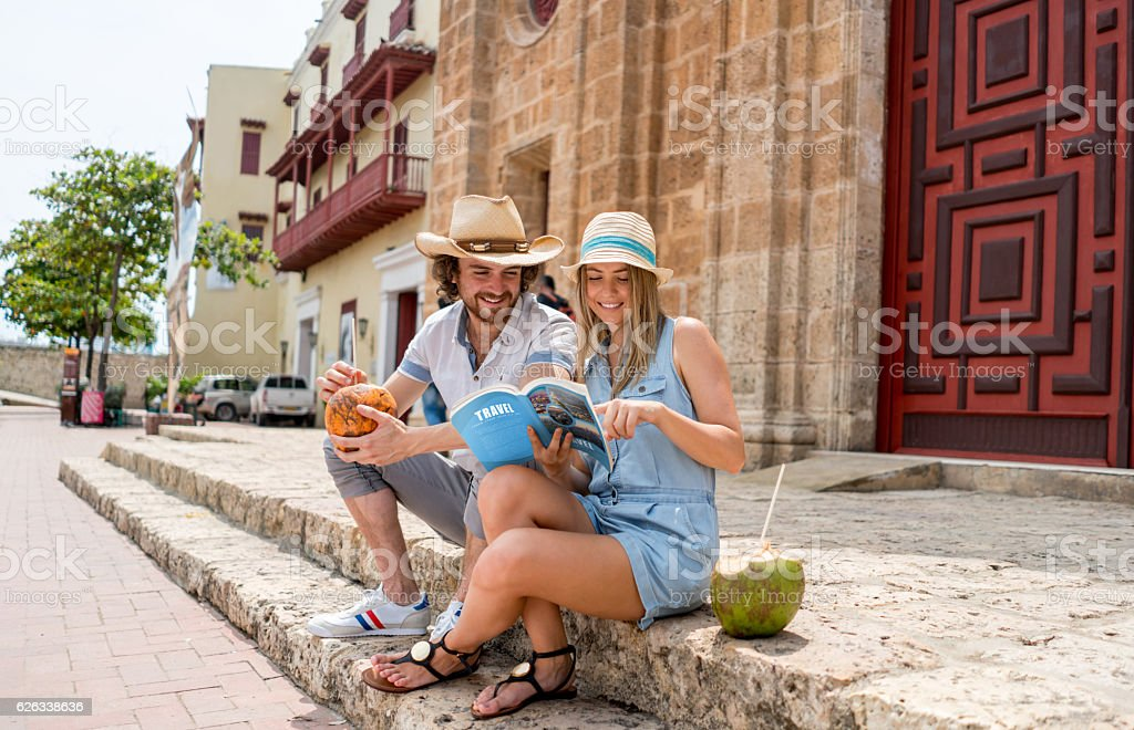 Couple of tourists looking at a travel guide while sitting outdoors -...