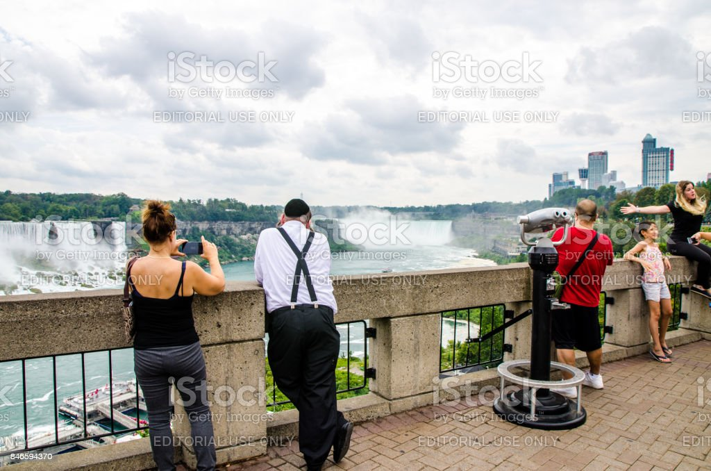 Tourists looking at and taking pictures of the Niagara Falls during summer day stock photo